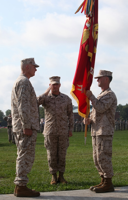 """Colonel Michael H. Brown (right), the commanding officer of Headquarters Battalion, 2nd Marine Division, relinquishes command of the battalion by ceremoniously passing the battalion's colors to Col. James B. """"Beau"""" Higgins during the Headquarters Battalion change of command on base, Aug. 3, 2012.  The Marines and sailors of Headquarters Battalion welcome Higgins, who recently completed a tour with the Combined Forces Special Operations Component Command – Afghanistan, as their new commanding officer. (U.S. Marine Corps photo by Cpl. Tommy Bellegarde)"""