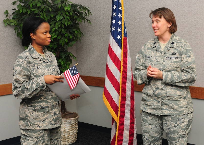 Airman 1st Class Princess Okai, 9th Force Support Squadron, food service apprentice is congratulated by Lt. Col. Connie May, 9th FSS Commander on becoming an American citizen at the Airman Family Readiness Center at Beale Air Force Base Calif., July 27, 2012. Okai said she joined the Air Force to travel and improve her education. (U.S. Air Force photo by Senior Airman Allen Pollard/Released)