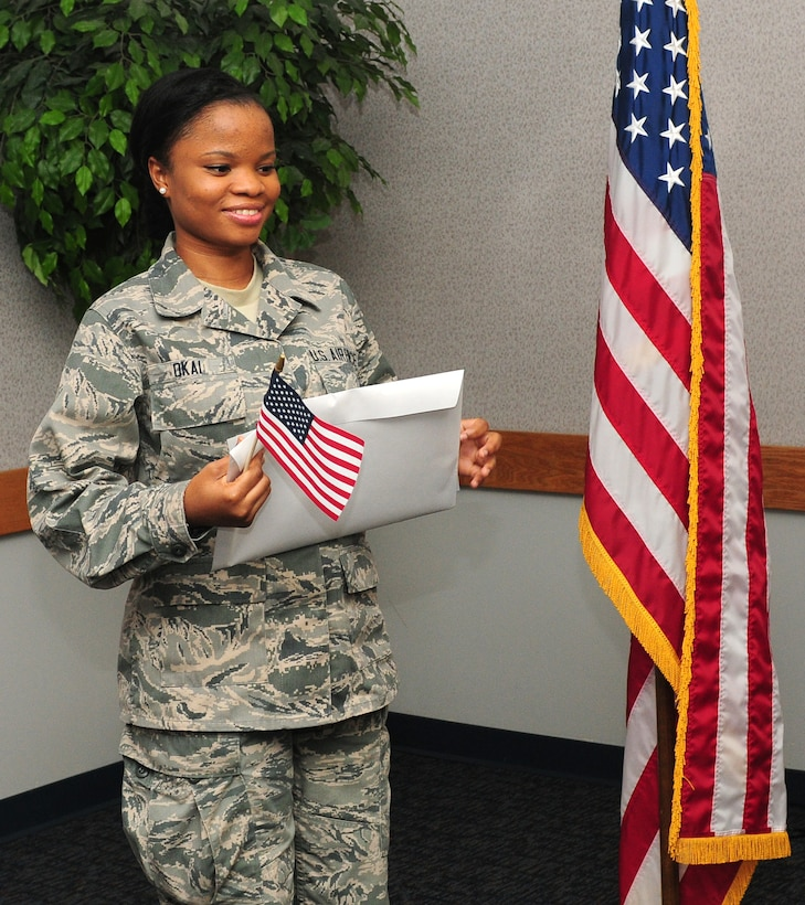 Airman 1st Class Princess Okai, 9th Force Support Squadron, food service apprentice holds an American flag and her citizenship paperwork at the Airman Family Readiness Center at Beale Air Force Base Calif., July 27, 2012. Okai was born in Ghana, West Africa, her and family moved to Long Island, N.Y. in 2007. (U.S. Air Force photo by Senior Airman Allen Pollard/Released)