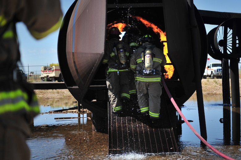 Firefighters with the Clovis, N.M. Fire Department enter the burn pit aircraft to extinguish a fire at Cannon Air Force Base, N.M., Aug. 2, 2012. The pit houses a replicated aircraft equipped with a propane tank and several igniters used to sustain training fires. (U.S. Air Force photo/Airman 1st Class Alexxis Pons Abascal)