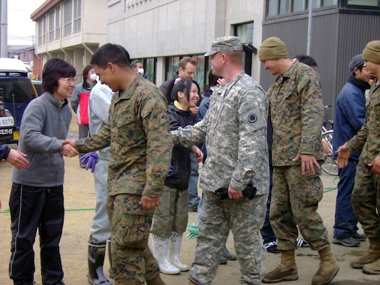 Local citizens of Ishinomaki City show their appreciation of Operation Tomodachi U.S. military members as they shake hands in mid March.  (Photo by Capt. Alex Glade)