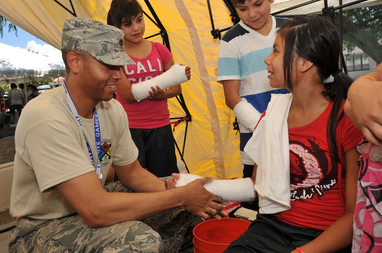 U.S Air Force Major William Peace a member of the Colorado Air National Guard 140th Medical Group cast kids from the Ute Mountain Ute Tribe as a demonstration of what it would be like to have to wear a cast if ever needed, Towaoc, Colo., July 25, 2012.  The 140th Medical Group is in Southwest Colorado this week hosting a health fair for the regions three Ute Tribes. (U.S. Air Force photo/Tech. Sgt. Wolfram M. Stumpf)