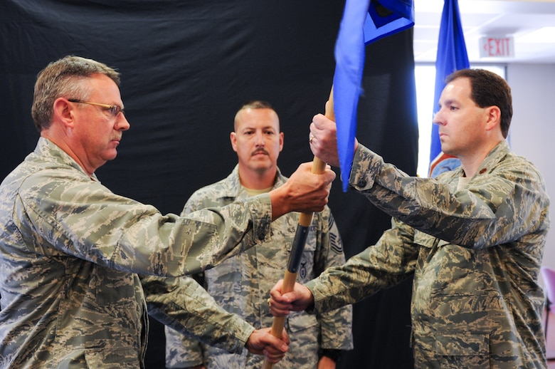 Col. Norm Brosi, left, commander of the 139th Airlift Wing's Mission Support Group, hands Maj. Greg Roberts the guidon for the 139th Security Forces Squadron during an assumption of command ceremony August 4, 2012 at Rosecrans Air National Guard Base, St. Joseph, Mo.  Roberts assumed command after more than 20 years of service.  (U.S. Air Force photo/Senior Airmen Kelsey Stuart)