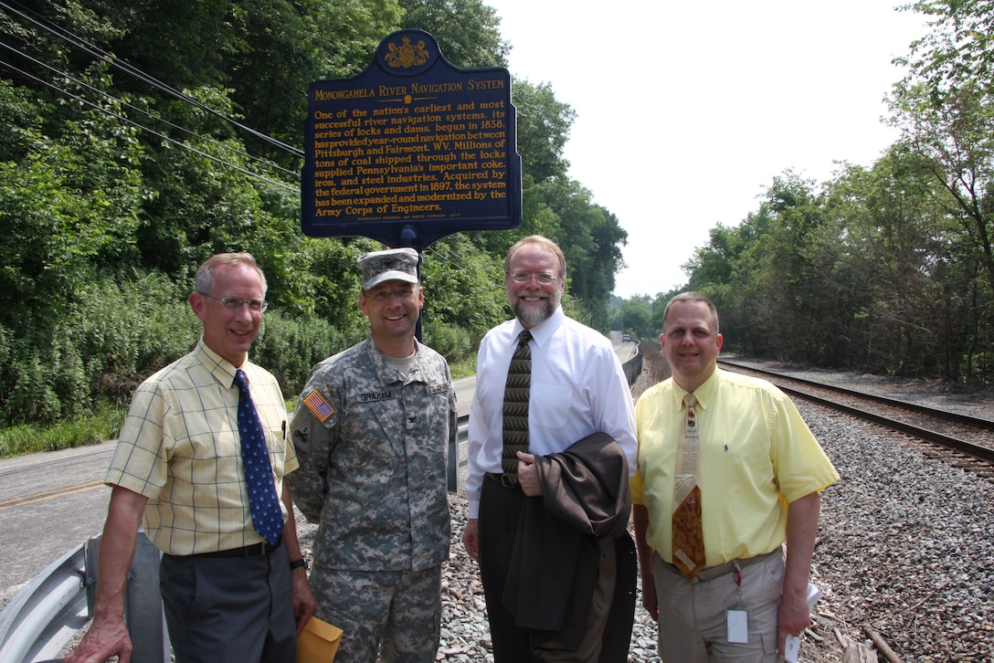 ELIZABETH, Pa. — Conrad Weiser, Environmental and Cultural Resources, Col. William Graham, U.S. Army Corps of Engineers Pittsburgh District Commander, Andrew Masich, Pennsylvania Historical and Museum Commission Chairman, and Brush Kish stand beneath the historical marker at the Elizabeth Locks. A historical marker recognizing the Monongahela River Navigation System as one of the nation's most historically successful river systems was dedicated June 18 at Locks and Dam 3, Monongahela River.