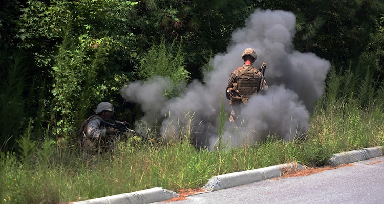 Marines with Company E, 2nd Battalion, 2nd Marine Regiment, 2nd Marine Division, get engulfed with black smoke from a faux improvised explosive device. Marines and sailors with Company E practiced counter-IED training July 30- August 2.