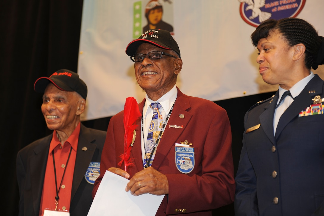Roscoe Brown Jr., Tuskegee Airman, and U.S. Air Force Brig. Gen. Stayce Harris, U.S. Africa Command mobilization assistant to the commander, accompany U.S. Air Force retired Lt. Col. James Harvey as he receives a certificate and red feather, giving him the title of honorary member of the Red Tails Aug. 1, 2012, at the Las Vegas Hotel and Casino, Nev. Harvey was presented with the title last year at a Tuskegee reunion in Orlando, Fla., but was unable to receive the award. (U.S. Air Force photo by Staff Sgt. William P.Coleman)