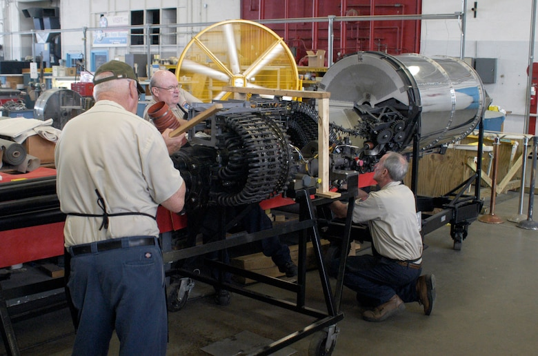 Restoration volunteers (from left to right) Ed Kienle, Garry Guthrie and Lou Thole load cartridges into the GAU-8/A drum. (U.S. Air Force photo)
