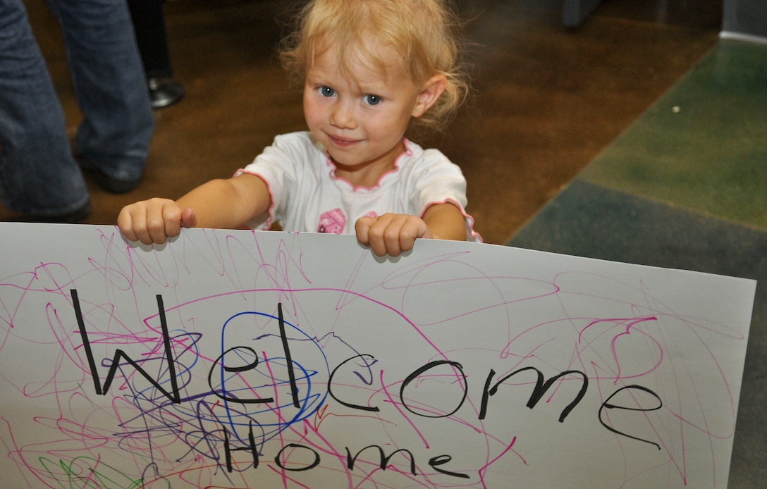 BUCKLEY AIR FORCE BASE, Colo. -- A little girl holds up her handmade sign to welcome home her big sister at the end of Operation Future Forces Aug. 4, 2012.  The children who participated, completed a shortened Basic Military Training and a simulated deployment by the time they returned home.  (U.S. Air Force photo by Staff Sgt. Nicholas Rau)