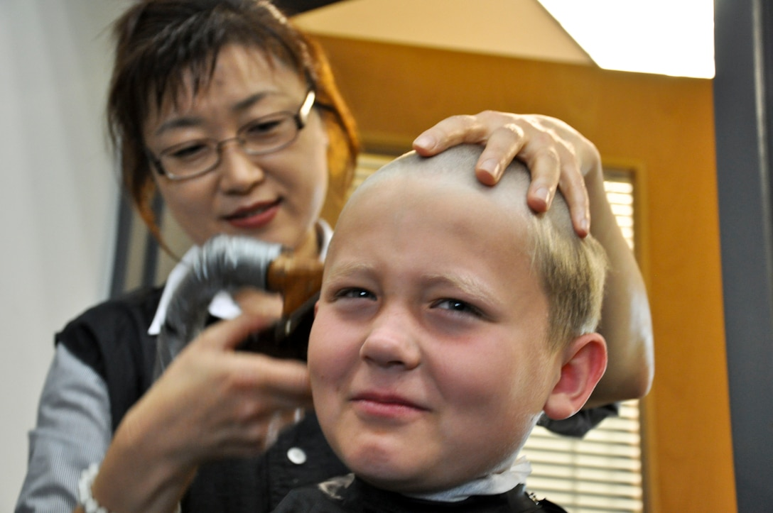 BUCKLEY AIR FORCE BASE, Colo. -- A child gets his haircut at the beginning of Operation Future Forces Aug. 4, 2012.  This event ran the children through a shortened Basic Military Training and a simulated deployment.  (U.S. Air Force photo by Staff Sgt. Nicholas Rau)