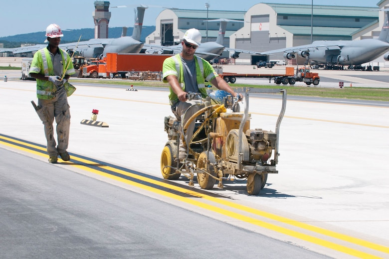 Contractors spray paint lines onto the edge of the newly aligned taxiway at the 167th Airlift Wing, Shepherd Field, Martinsburg WV, July 25, 2012.  Final touches are being made to the taxiway, which was recently realigned and extended; the final C-5 conversion construction project at the base. (Air National Guard photo by Master Sgt. Emily Beightol-Deyerle)