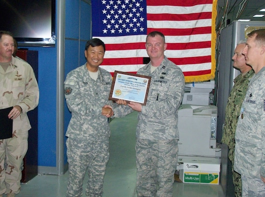 172d AW Capt. Keith Herrington (right) is shown receiving the Company Grade Officer of the Quarter Award while serving in support of Operation Enduring Freedom in Arifjan, Kuwait.  Whle deployed, Herrington has been serving in the CENTCOM DDOC (Deployment Distribution and Operations Center).