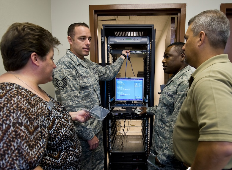 Air Force Engineering and Technical Service employees train active duty members on how to program a computer based scenario simulator on Barksdale Air Force Base, La., Aug. 9. AFETS recruits mostly prior military members to remain as part of the force and work alongside active duty maintenance and communications Airmen. (U.S. Air Force photo/Staff Sgt. Chad Warren)(RELEASED)