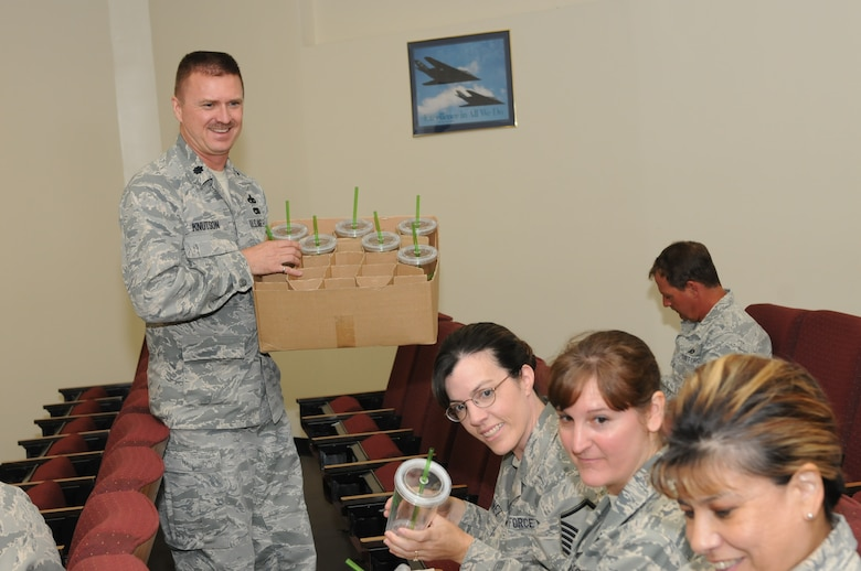 "Lt. Col. Michael Knutson passes out reusable cups on base Aug. 4 to help wing members reduce their use of disposable water bottles. The cups promote awareness of the Environmental Management System by including the EMS mission statement printed on the side in green letters - ""Continual improvement of our processes and practices that enable us to reduce our environmental impacts, increase our operating efficiency wile executing our mission."" Knutson will distribute more cups when he makes EMS presentations at future unit training assemblies. (U.S. Air Force photo/ Tech. Sgt. Hollie Hansen)"