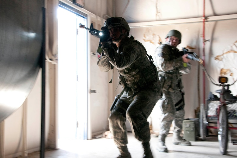 Senior Airman Samuel Alanis (left) and Staff Sgt. Brad Guzman seek out a simulated active shooter during an exercise at the 162nd Fighter Wing in Tucson Ariz. Both troops are from the Security Forces Squadron, whose members were being trained and evaluated in response to a simulated active shooter.  (U.S. Air Force photo/Master Sgt. David Neve)