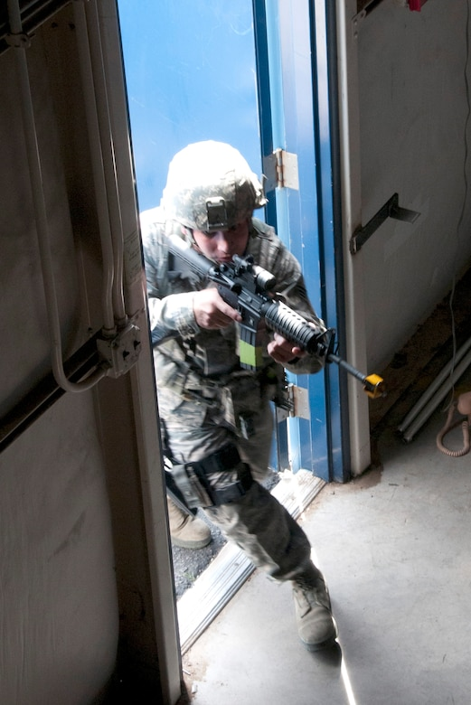 Senior Airman Steven Nunez storms through a warehouse door during an active shooter exercise at the 162nd Fighter Wing in Tucson Ariz. Nunez is from the Security Forces Squadron, whose members were being trained and evaluated in response to a simulated active shooter threat.  (U.S. Air Force photo/Master Sgt. David Neve)