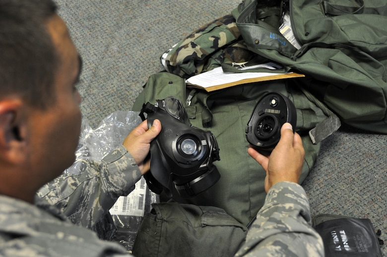 A new member of Team Osan inspects his gas mask filter at the 51st Logistics Readiness Squadron Individual Protective Equipment facility during combat in-processing at Osan Air Base, Republic of Korea, Aug. 7, 2012. IPE is the minimum personal clothing and equipment needed to protect wearers from most chemical, biological, radiological, nuclear and high yield hazards. (U.S. Air Force photo/Airman 1st Class Alexis Siekert)