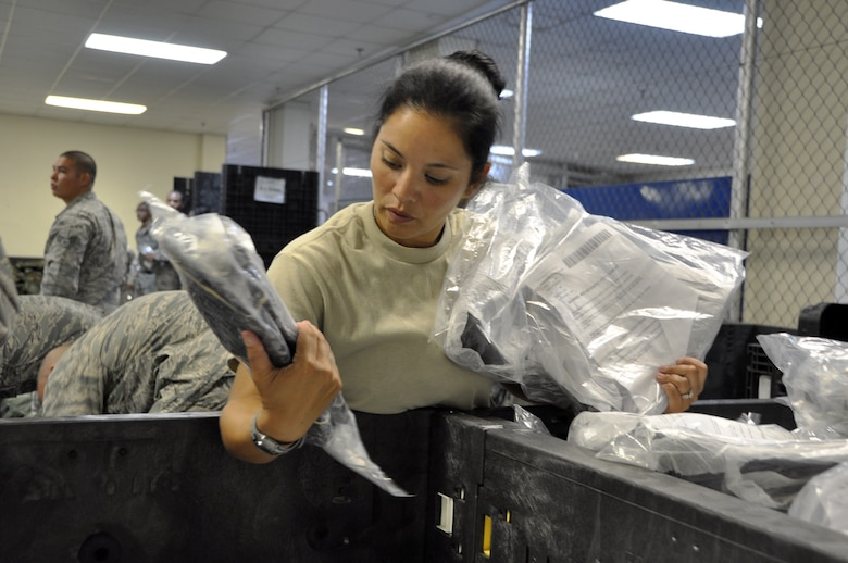 Tech. Sgt. Mariya Cavazos-Munguia, 51st Comptroller Squadron customer service NCO in charge, selects a pair of real-world over boots for her Individual Protective Equipment bag at Osan Air Base, Republic of Korea, Aug. 7, 2012. The 51st Logistics Readiness Squadron IPE facility issues gear to all Osan service memebers during their first week of combat in-processing. (U.S. Air Force photo/Airman 1st Class Alexis Siekert)