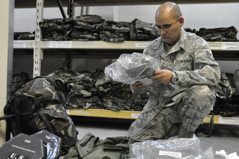 Staff Sgt. Daniel De La Torre, packs his Individual Protective Equipment during combat inprocessing at Osan Air Base, Republic of Korea, Aug. 7, 2012. All service members in-processing Osan must visit the 51st Logistics Readiness Squadron IPE facility to be issued exercise and real world gear.  De La Torre is a 51st Aerospace Medicine Squadron medical technician. (U.S. Air Force photo/Airman 1st Class Alexis Siekert)