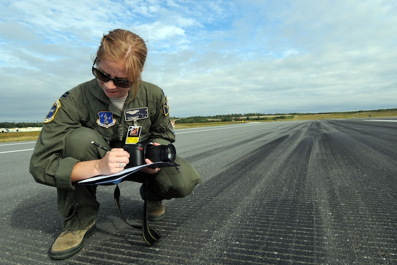 """JOINT BASE ELMENDORF-RICHARDSON, Alaska - Capt. Allison Snow, a C-17 pilot with the Alaska Air National Guard's 249th Airlift Squadron measures the accuracy of a C-17 landing on the flight line here Aug. 11, 2012. Snow was a lead judge for aircraft landings in a """"Moose Shoot"""" -- an airdrop and landing competition between the 176th Wing's airlift squadrons as well as their active-duty Air Force associate units, the 517th and 537th airlift squadrons. (National Guard Photo by Tech. Sgt. Jennifer Theulen)"""