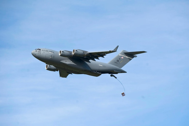 """JOINT BASE ELMENDORF-RICHARDSON, Alaska - A C-17 drops a training container delivery system at the Malamute Drop Zone here Aug. 11, 2012. The Aircraft was participating in a """"Moose Shoot"""" -- an airdrop and landing competition between the 176th Wing's airlift squadrons as well as their active-duty Air Force associate units, the 517th and 537th airlift squadrons.  (National Guard photo by Master Sgt. Shannon Oleson)"""