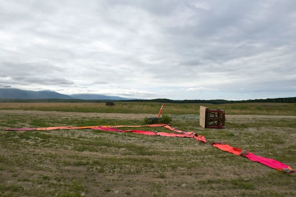 "JOINT BASE ELMENDORF-RICHARDSON, Alaska - Two training container delivery systems (CDS) lay next to a target point at the Malamute Drop Zone here Aug. 11, 2012. The CDSs are attached to parachutes and are used in airdrops by military cargo aircraft. During wartime and humanitarian missions, they carry supplies such as food or ammunition to areas that cannot otherwise be reached. These CDSs were used by Alaska Air National Guard's 176th Wing's airlift squadrons participating in a ""Moose Shoot"" -- an airdrop and landing competition. Also participating were the JBER-based 517th and 537th airlift squadrons of the active-duty Air Force. (National Guard photo by Master Sgt. Shannon Oleson)"