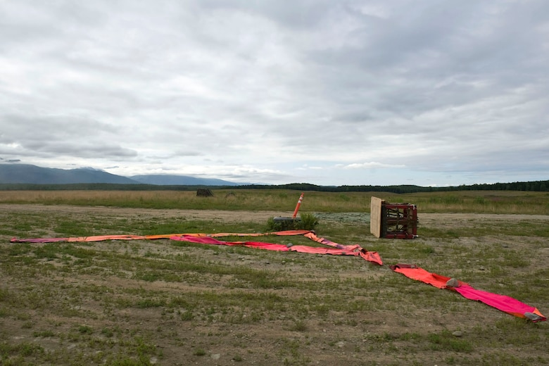 """JOINT BASE ELMENDORF-RICHARDSON, Alaska - Two training container delivery systems (CDS) lay next to a target point at the Malamute Drop Zone here Aug. 11, 2012. The CDSs are attached to parachutes and are used in airdrops by military cargo aircraft. During wartime and humanitarian missions, they carry supplies such as food or ammunition to areas that cannot otherwise be reached. These CDSs were used by Alaska Air National Guard's 176th Wing's airlift squadrons participating in a """"Moose Shoot"""" -- an airdrop and landing competition. Also participating were the JBER-based 517th and 537th airlift squadrons of the active-duty Air Force. (National Guard photo by Master Sgt. Shannon Oleson)"""