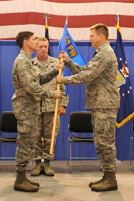 New York Air National Guard Lt. Col. Michael Smith (right) receives the 174th Fighter Wing Maintenance Group Guideon from 174th Fighter Wing Commander Col. Greg Semmel during a change of command ceremony held on August 11, 2012 at Hancock Field Air National Guard Base.  Lt. Col. Smith assumed command of the Maintenance Group from Col. John Balbierer. Lt. Col. Smith previously served as commander of the 138th Fighter Squadron stationed on Hancock Field.. (Photo by New York Air National Guard Staff Sgt. James N. Faso II/Released)