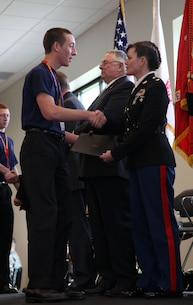 Major Heather Cotoia presents poolee William Corrin with his certificate and congratulates him on his successful entrance into the United States Marine Corps at Vancouver, WA on April 28. Poolees from all branches of service were presented with a coin from Brig. Gen. Yoo and a certificate from their branch of service before collectively taking the oath of enlistment.