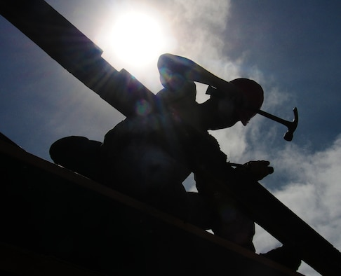 ANDERSEN AIR FORCE BASE, Guam— A member of the 554th REDHORSE Squadron drives a nail as other members frame a building during framing training, July 30. When deployed, members of the 554th RHS are required to build large structures constructed out of wooden materials. Training that Airmen receive will allow them to know the basics before being required to build down range.  (U.S. Air Force photo by Senior Airman Benjamin Wiseman/Released)