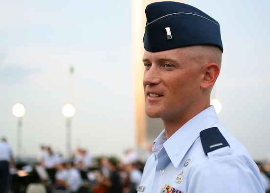 First Lt. Michael Lemoire, U.S. Air Force Honor Guard flight commander, participates in a rare experience of conducting the U.S. Air Force Band concert ensemble, Aug. 3, at the Air Force Memorial in Arlington Va.  Lemoire set aside his honor guard duties for an evening to put his musical education and background to the test while leading the 53 piece group ensemble. (Courtesy photo by Amelia Harrington)