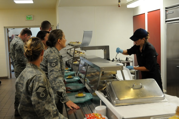 A food service worker serves wing members during lunch Aug. 5.  The new contract, awarded in late July, brings a new crew of civilian workers who will assist Services personnel with the preparation and serving of more than 1,000 meals each drill weekend.