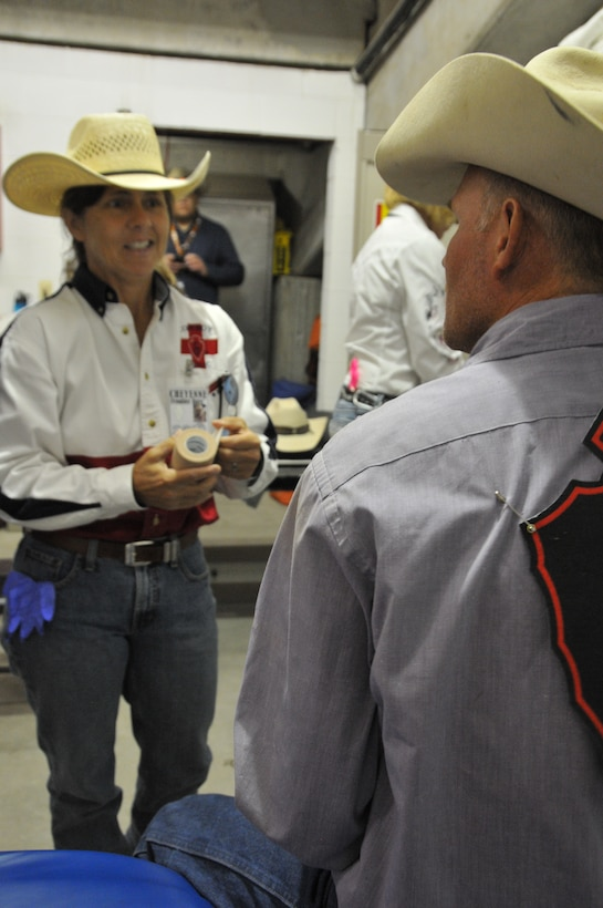Lt. Col. Julie Resheske, 187th Aeromedical Evacuation Squadron flight nurse, assists a wild horse race contestant with a shoulder wrap before competing at Cheyenne Frontier Days July 25, 2012. Resheske has volunteered with the cowboy medics for 10 years. (U.S. Air Force photo by 1st Lt. Rusty Ridley)