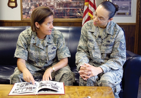 Col. Stella Smith and Tech. Sgt. Malika Likavec graduated from City Honors High School, Buffalo, N.Y. and talk about their respective high school days as they thumb through Colonel Smith's yearbook recently.  Colonel Smith, squadron commander, and Sergeant Likavec , a maintenance scheduler, have served the Air Force around the world on a journey that brought both to Tinker where a squadron picnic discussion about Sergeant Likavec's Buffalo Bills sweatshirt revealed their shared hometown beginnings. (Air Force photo by Margo Wright)