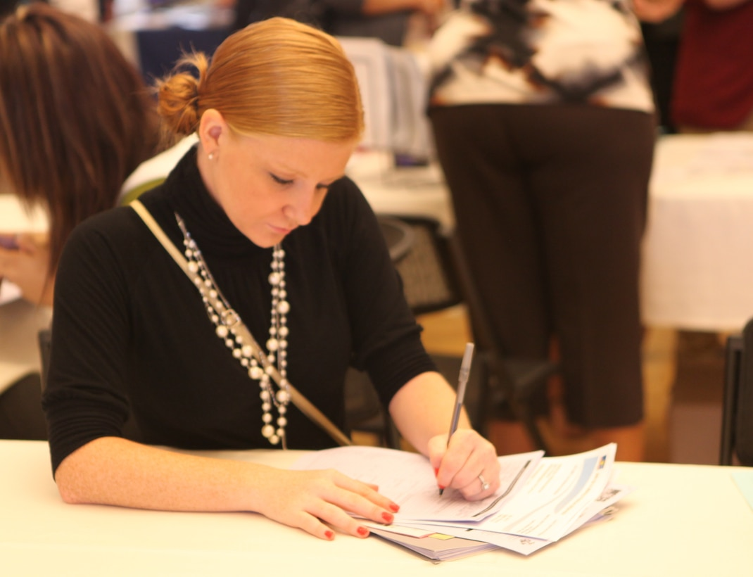 A military spouse fills out an application for a job at the Marston Pavilion aboard Marine Corps Base Camp Lejeune during the Military Spouse Business Alliance Hiring Fair and Career Forum Aug. 9. Many employers held interviews on the spot and there where staff members present who gave resume-building advice.