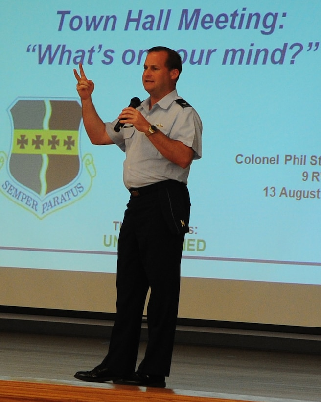 The commander of the 9th Reconnaissance Wing, Col. Phil Stewart, hosts a town hall meeting for Airmen and their families at the Community Activity Center, Beale Air Force Base, Calif., August 14, 2012. During the meeting department heads briefed the new Food Transition Initiative, back to school, the Eagle Eyes program, housing privatization and welcomed questions from guests. (U.S. Air Force photo by Senior Airman Shawn Nickel/Released)