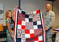 Katherine Trowbridge, Air Force Test Center Contracting Directorate resource advisor, presents Tech. Sgt. Lawrence Bredwell, 31st Test and Evaluation Squadron fighter aircraft crew chief, with a Quilt of Valor during a presentation ceremony in Building 2800 on Aug. 8. (U.S. Air Force photo by Jet Fabara)