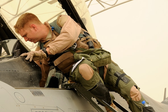 "South Carolina Air National Guard Maj. Ian ""Chester"" Toogood, an F-16 pilot, climbs out of his jet after returning from a mission over Afghanistan on Aug. 5, 2012. Members of the 169th Fighter Wing at McEntire Joint National Guard Base, S.C., are deployed to KAF in support of Operation Enduring Freedom. Swamp Fox F-16's, pilots, and support personnel began their Air Expeditionary Force deployment early April to take over flying missions for the air tasking order and provide close air support for troops on the ground in Afghanistan. (U.S. Air Force photo/Tech. Sgt. Stephen Hudson)"