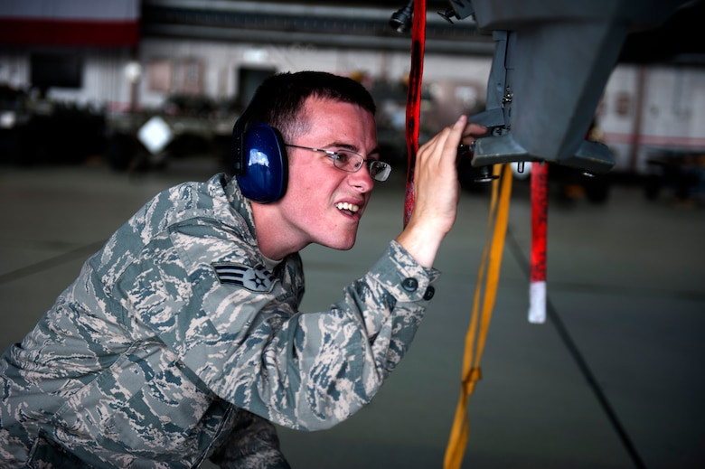 SPANGDAHLEM AIR BASE, Germany – Senior Airman Jared Schiffman, 480th Aircraft Maintenance Unit weapons load crew member, loosens a bolt in preparation to mount a Mk-82 bomb during a weapons load competition here Aug. 10.  The 480th and 81st AMUs host and participate in the timed competition once a quarter to see which unit has the fastest and most efficient weapons load crew.  The winners of the competition earn bragging rights as the best crew and a trophy until the next quarter. (U.S. Air Force photo by Airman 1st Class Gustavo Castillo/Released)