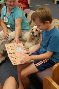 "Jack Greene, 7, reads his favorite book to therapy dog, Davy, and handler Shirley Colman, founder of Independent Therapy Dogs, Inc. at the library Aug. 8 aboard Marine Corps Recruit Depot San Diego. ""Ruff"" Readers is a program developed by ITD, Inc. to help children learn to read and promote responsible pet ownership."