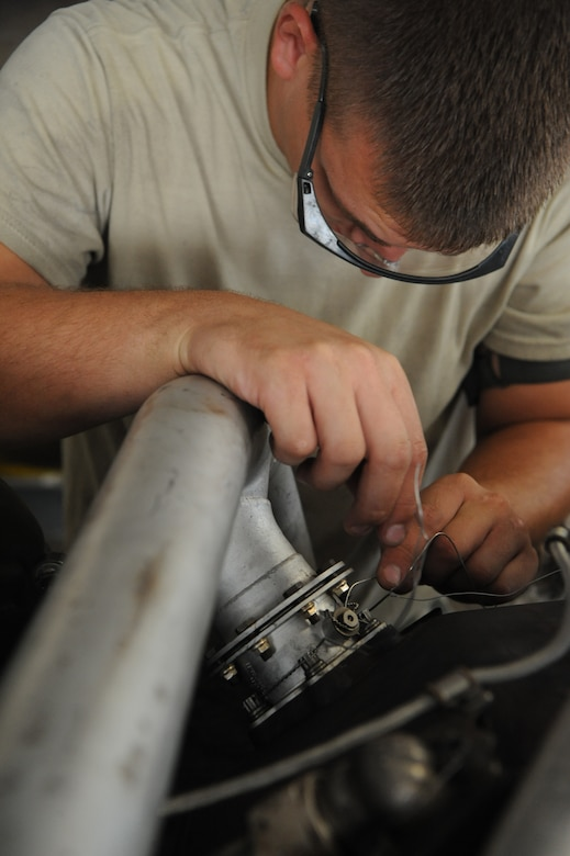 Senior Airman Colton Chandler, 2nd Maintenance Squadron aerospace propulsion craftsman, runs safety wire through a bolt connecting an air duct to an engine on Barksdale Air Force Base, La., Aug. 13. The safety wire is connected to other bolts to keep them from coming loose due to the vibrations of the engine. (U.S. Air Force photo/Airman 1st Class Micaiah Anthony)(RELEASED)
