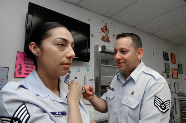 Staff Sgt. Caroline Mejia, 359th Medical Group, receives an immunization from Staff Sgt. Alex FarFan, 359th Medical Group allergy immunization technician, at the Joint Base San Antonio-Randolph Clinic April 2. (U.S. Air Force photo by Don Lindsey)