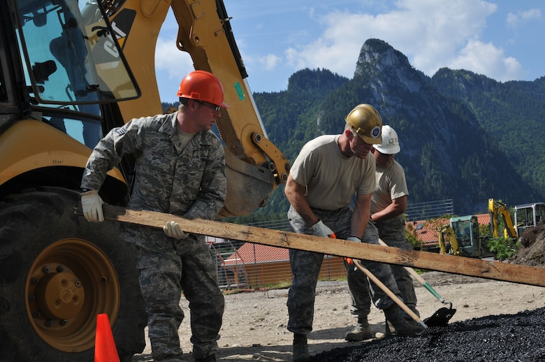 Members of the Wyoming Air National Guard's 153rd Civil Engineer Squadron Staff Sgt. Robert Parrish, Chief Master Sgt. Emery Edwards and Master Sgt. Andy Salyards smooth asphalt Aug. 13, 2012, at the NATO School recreation center, Oberammergau, Germany. Airmen from the 153rd CES are putting their skills to work as they conduct their annual training. (U.S. Air Force photo by Staff Sgt. Natalie Stanley)