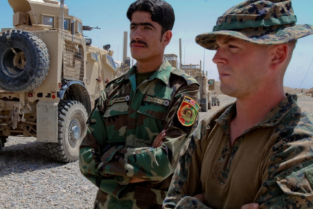 Afghan National Army 1st Lt. Asrar Hussain, an officer with 1st Kandak, 1st Brigade, 215th Corps, stands with 1st Lt. Stephen Huff, platoon commander, Weapons Company, 1st Battalion, 1st Marines, Regimental Combat Team 6, during a briefing, Aug. 15, 2012. Huff developed a friendship with Hussain and the other Afghan soldiers while working in Trek Nawa, a known insurgent stronghold between the Marjah and Nawa districts.