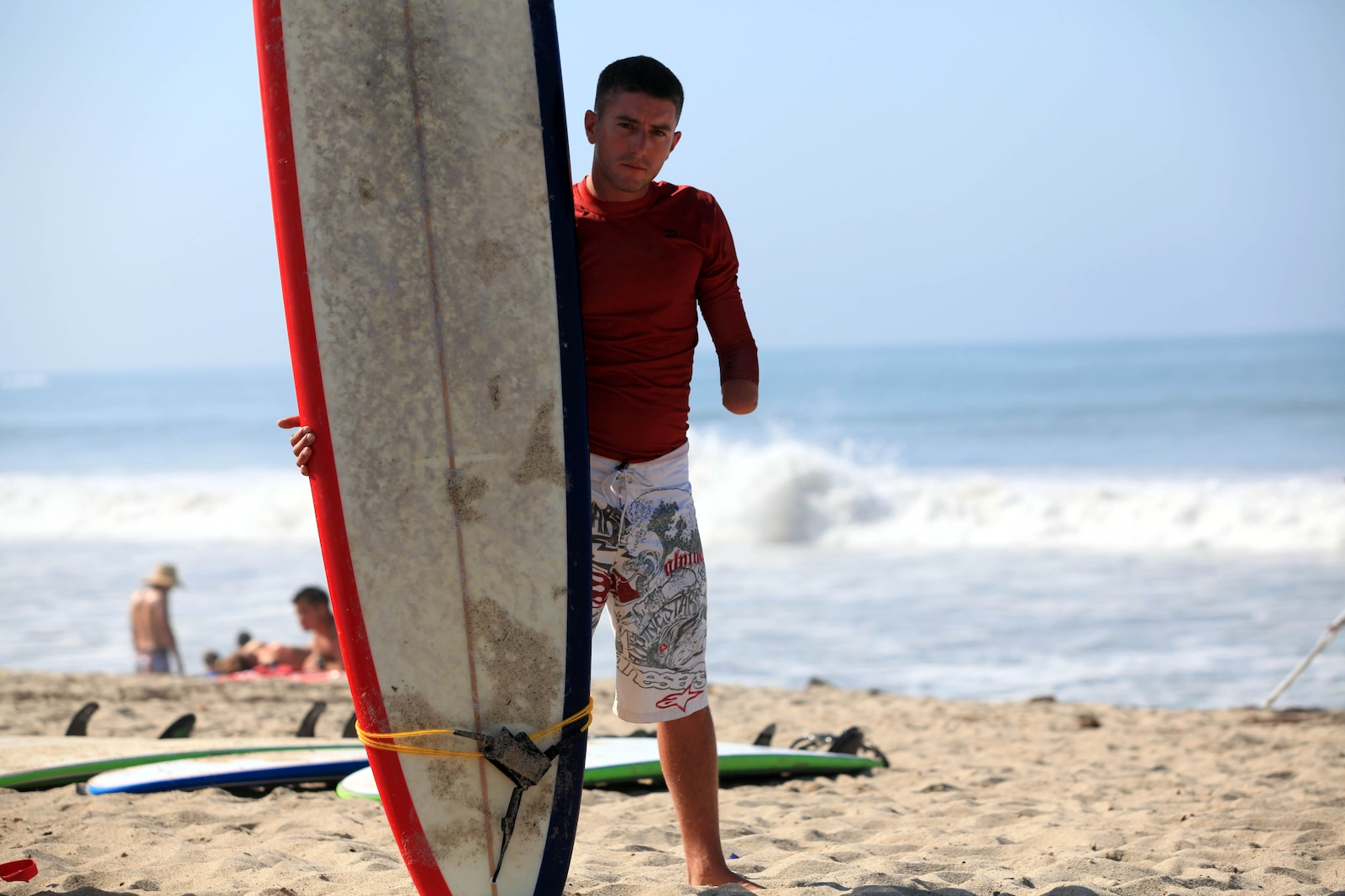 Wounded Warrior, Sgt. Michael Spivey, a combat engineer with 1st Combat Engineer Battalion, stands with his surfboard, waiting for another participant, before attacking the Pacific Ocean waves during a three-day surf camp at Camp Pendleton's San Onofre Beach, Aug. 12. Operation Amped held the sport therapy camp to provide surfing lessons to rehabilitating injured service members and their families.