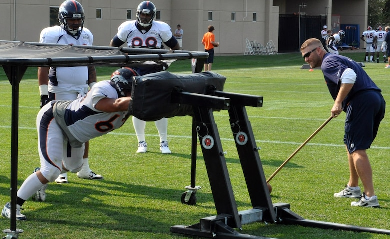 """ENGLEWOOD, Colo. – Benjamin Garland, Denver Broncos defensive end, hits the """"sled"""" during training camp Aug. 14, 2012 at the Broncos training facility. Garland is also a lieutenant with the 140th Wing Public Affairs, Buckley Air Force Base. (U.S. Air Force photo by Staff Sgt. Nicholas Rau)"""