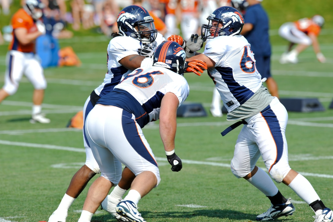 ENGLEWOOD, Colo. – Benjamin Garland, right, Denver Broncos defensive end, participates in a drill during training camp Aug. 14, 2012 at the Broncos training facility. The best advice Garland said he's received during training camp has been from special team's captain and weak outside linebacker Wesley Woodyard. Who told him to continue to work as hard as he has been and to keep pushing it to that next level every time he steps out on the field. (U.S. Air Force photo by Senior Airman Christopher Gross)