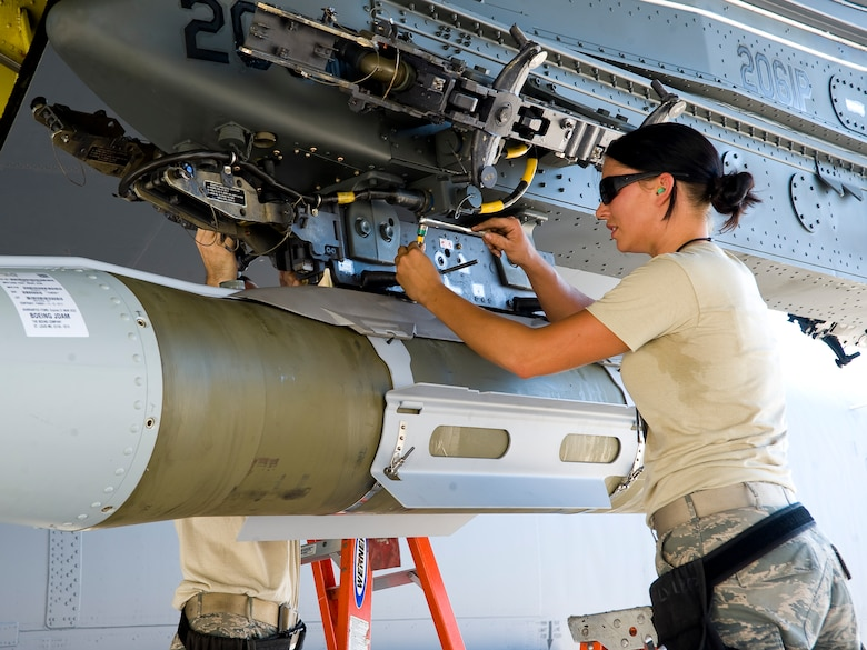 Senior Airman Erin Bernik, 2nd Maintenance Operations Squadron weapons standardization section, attaches an inert GBU-31 joint direct attack munition to a heavy storage adapter beam under the wing of a B-52H Stratofortress on Barksdale Air Force Base, La., Aug 14. The HSAB contains connections that allow the aircraft to communicate with the computer systems in the smart bombs. The weapon load is part of exercise Combat Hammer, meant to evaluate the generation and employment of guided munitions. (U.S. Air Force photo/Staff Sgt. Chad Warren)(RELEASED)