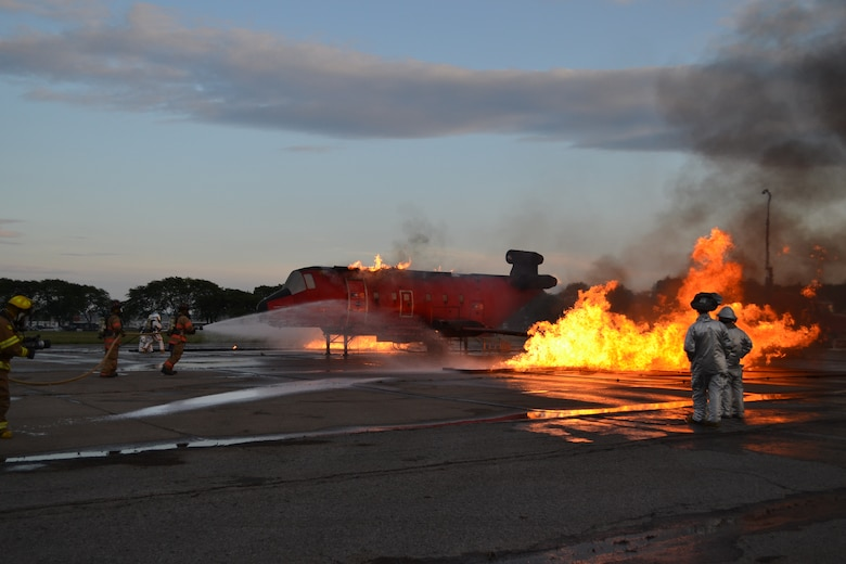 Firefighers from Hancock Field Air National Guard Base, Syracuse, New York respond to a simulated aircraft fire as part of a large scale Tri-County Major Accident Response Exercise (MARE) held on 11 August 2012.The exercise involved two simultaneous exercise events, a building collapse, simulated chemical spill and bomb search in downtown Syracuse and a simulated plane crash and fire at Syracuse Hancock International Airport. (Photo by New York Air National Guard Lt. Col. Catherine Hutson/Released)