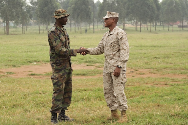 1stLt. Herman Davis, the platoon commander of the engineer platoon from Battalion Landing Team 1st Battalion, 2nd Marine Regiment, 24th Marine Expeditionary Unit, shakes hands with a member of the Uganda People's Defense Force as they prepare for another day of training in Uganda.  Davis is serving as the team leader of a small group of Marines from the 24th MEU who went to Uganda to participate in a training mission as part of the African Union Mission in Somalia training Ugandan forces in basic marksmanship, small unit tactics, and engineering.  The 24th MEU is deployed with the Iwo Jima Amphibious Ready Group as a theater reserve and crisis response force in the U.S. Central Command and 5th Fleet areas of responsibility.