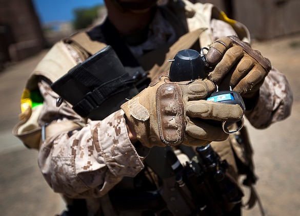 U.S. Marine Lance Cpl. Tory Martin, a rifleman with 3rd Platoon, India Company, 3rd Battalion, 3rd Marine Regiment, and 20-year-old native of Twentynine Palms, Calif., replaces the safety pin of a Stingball grenade after using it during a non-lethal weapons training scenario in a simulated urban village on Marine Corps Training Area Bellows, Hawaii, Aug. 15, 2012. The training was part of a two-week test readiness review fielded by the Quantico, Va.-based Joint Non-Lethal Weapons Directorate and the Marine Corps Forces, Pacific Experimentation Center. The DoD Non-Lethal Weapons Program, headed by Commandant of the Marine Corps Gen. James Amos, trains operating forces on escalation of force options to minimize casualties and collateral damage, said Kelley Hughes, a directorate spokesperson.